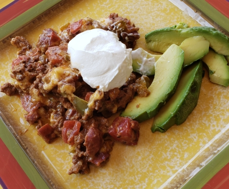 taco casserole on a plate with sour cream and fresh avocado